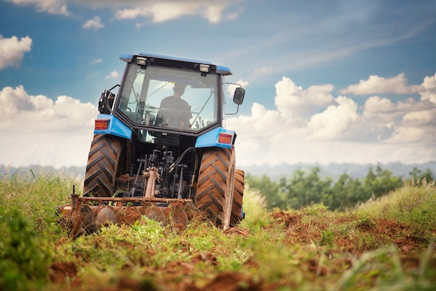 A blue tractor working on farm land