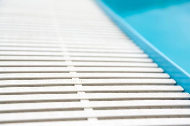 青い透明なプールの水面と白いプラスチック製のサイドグレーティング。あなたの製品のモンタージュのために