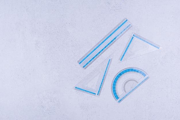 Righelli rettilinei e triangolari trasparenti blu su superficie grigia