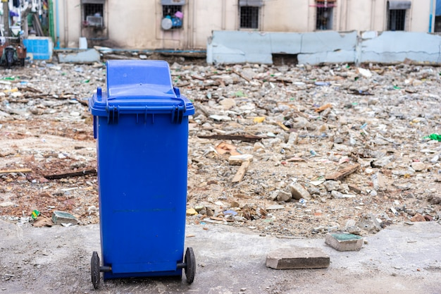 Blue trashcan with old building