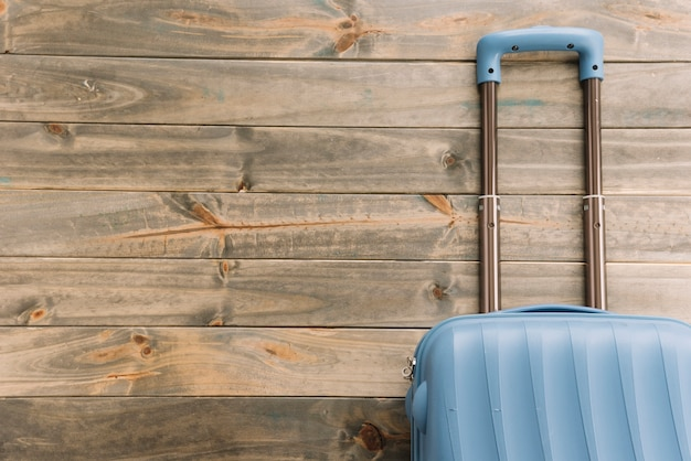 Blue travel suitcase against wooden background