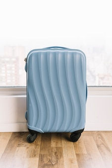 Blue travel suitcase near the window on wooden floor