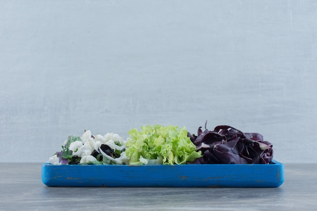 Blue tray of chopped cabbage, cauliflower and amaranth on marble.