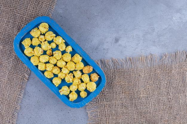 Синий поднос с горсткой желтых конфет из попкорна на кусках ткани на мраморной поверхности
