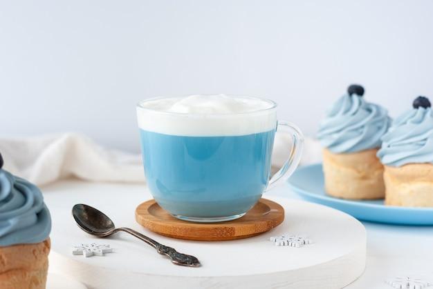 朝食にミルクとケーキを添えたバタフライピーティーのブルーのトレンディなドリンク