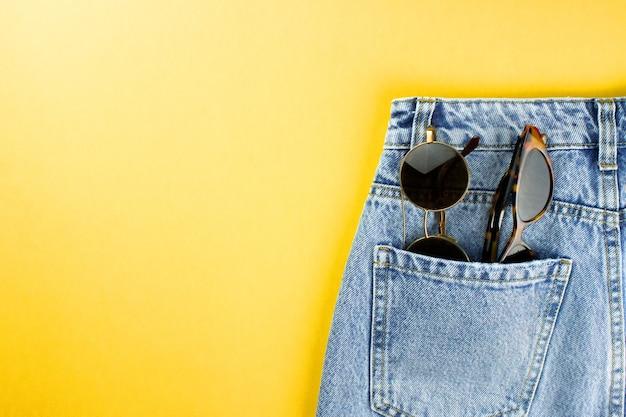 Синие джинсы унисекс с плоской белой этикеткой лежат на желтом фоне с копией пространства для текста, логотипа.