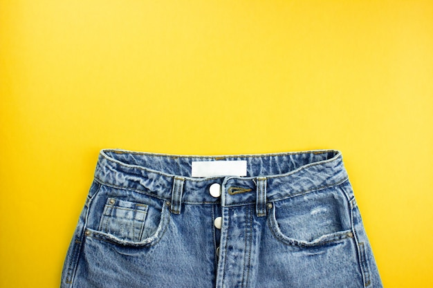 Blue unisex jeans with white label flat lay on yellow background with copy space for text, logo.