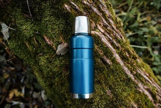 블루 진공 보온병 야외. 녹색 이끼와 나무 배경입니다. 평면도. 개념 뜨거운 음료, 하이킹