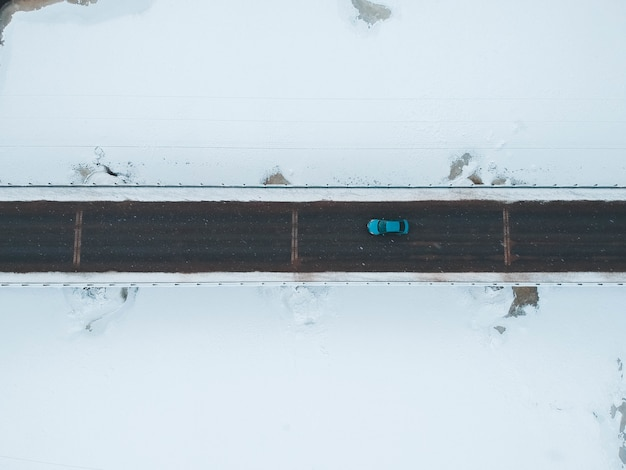 Blue vehicle on road in winter