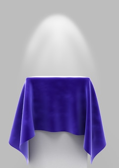 照明付きの灰色の背景の正方形の台座に青いベロア布
