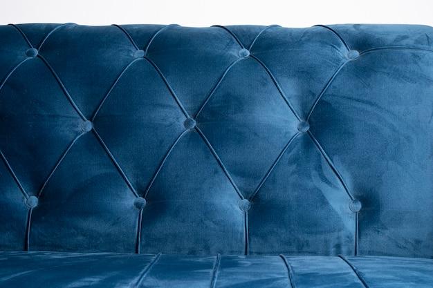 沈んだボタンと青いベルベットのソファの質感