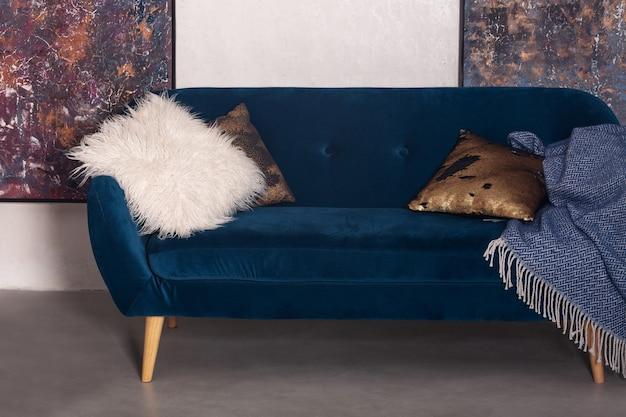 平らな内部に枕が付いている青いビロードのソファー