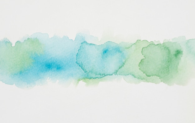 Blue and verdant spots of paints on white paper