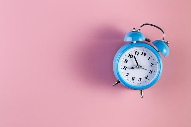 Blue vintage alarm clock on light pink color background