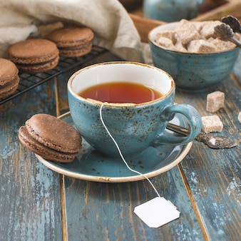 Blue vintage tea bag cup on wooden table, craft, macaroons cookies, sugar lumps