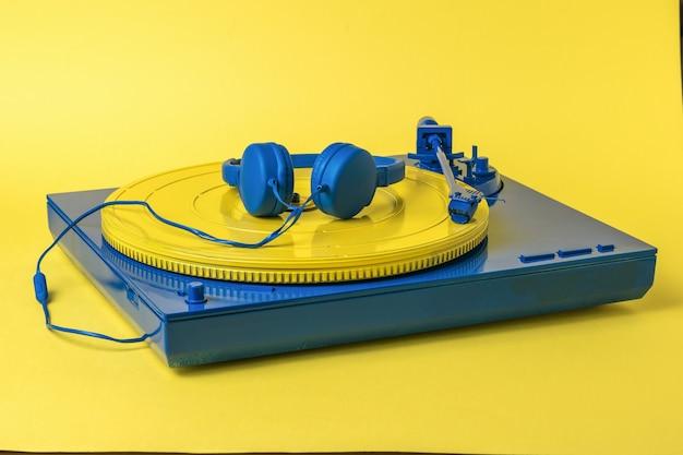 黄色のディスクと黄色の表面に青いヘッドフォンを備えた青いビニールレコードプレーヤー。レトロな音楽機器。