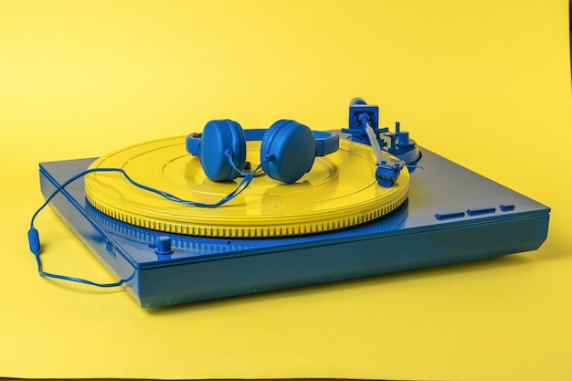 Blue vinyl record player with a yellow disc and blue headphones on a yellow surface. retro music equipment.