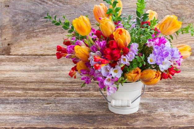 木製のテーブルに青、紫、赤のフリージアとオレンジ色のチューリップの花
