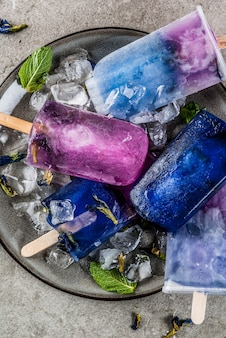Blue and violet ice cream popsicles with butterfly pea flower tea