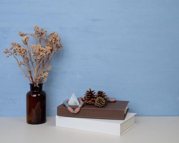 Место для копирования на синей стене для дизайна или текста, белые и коричневые книги, сушеный цветок в стеклянной банке, сосновые шишки и старинный камень, сидящий на деревянном столе
