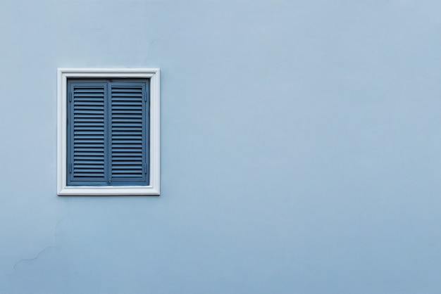 Blue wall of the house with a closed window left and details.