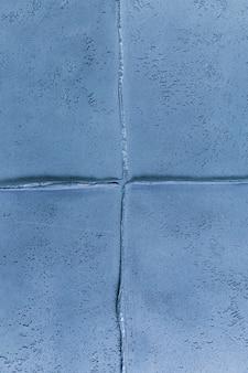 大まかな質感を持つ青い壁の接合箇所
