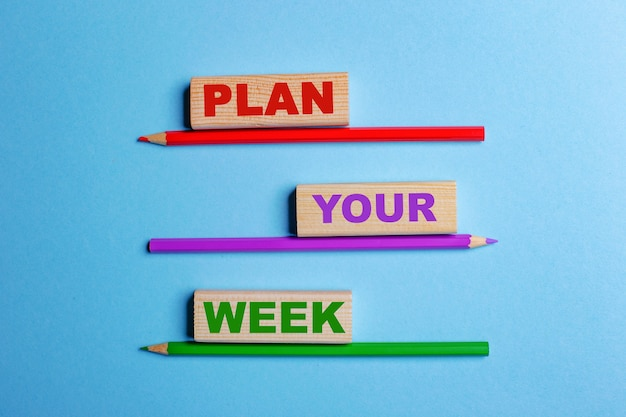 On a blue wall, three colored pencils, three wooden blocks with text plan your week