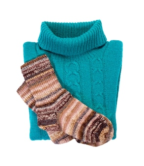 Blue warm knitted sweater with a pattern and socks. isolate on white. warm winter clothes.