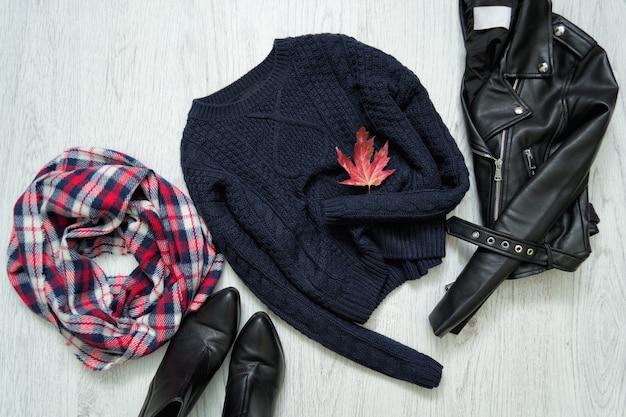 青い暖かいセーター。黒のジャケット、市松模様のスカーフ、ブーツ。ファッショナブルなコンセプト