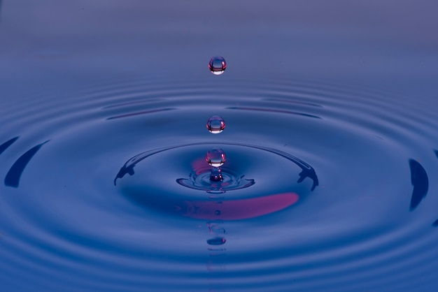 Blue water drops frozen in the air and forming ripples on the liquid surface