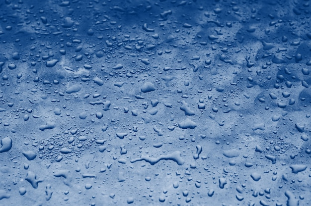 Blue water drops texture on the glass background. classic blue toning trend 2020