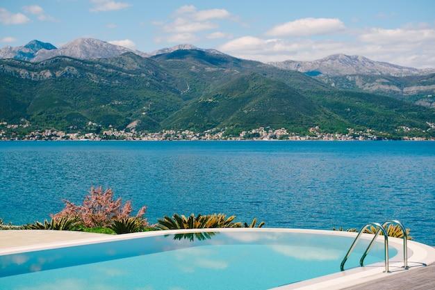 海の山々と空を背景にプールの青い水