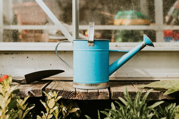 Blue watering can with trowel on wooden table