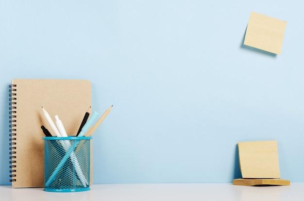 Синие, белые и черные карандаши, ручки на подставке, крафт-блокнот на белом столе, наклейки на голубиной стене, рабочий стол офиса.