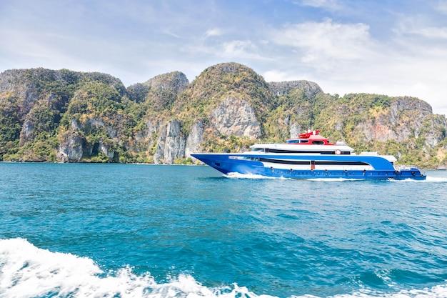 파란색 흰색과 빨간색 악센트가 있는 유람선 열대 산악 섬을 배경으로 바다를 항해하는 유람선