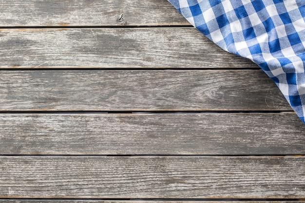 파란색 흰색 체크무늬 식탁보가 나무 식탁에 올려져 있습니다.