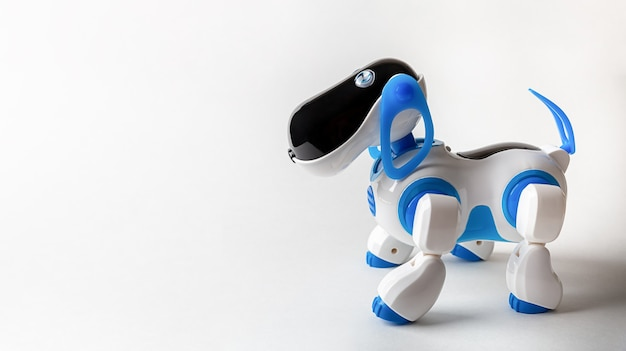 Blue and white robot dog with remote control on a white paper background closeup with copy space.