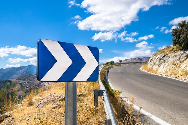 Blue white street sign showing directions next to a road with a scenic