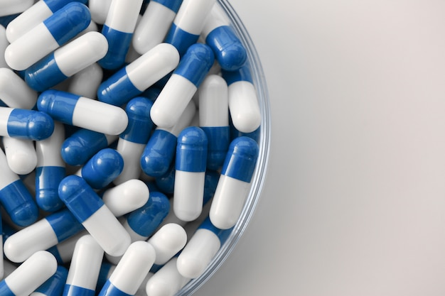 Blue white tablets or capsules in transparent container on the table
