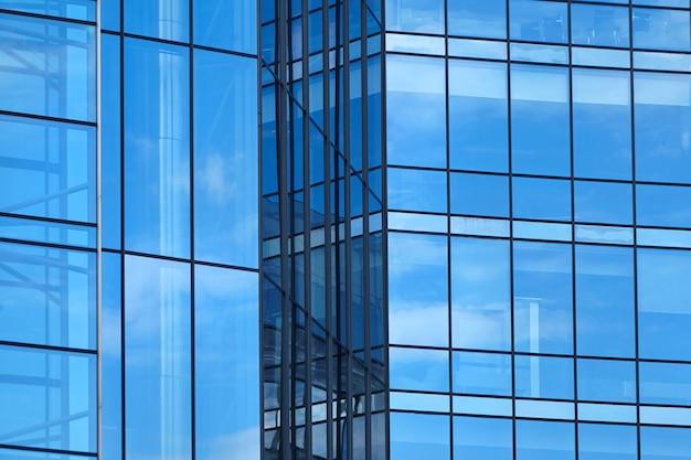 高層ビルの青い窓。近代的なオフィスビルのガラスのファサードの断片