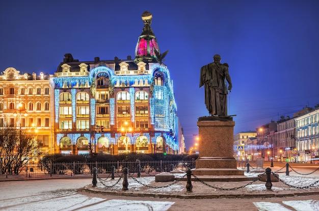 Синяя зимняя ночь в доме зингера в новогодних декорациях и памятник кутузову в санкт-петербурге.