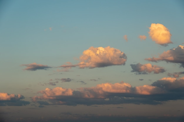 Blue winter sky sunset with separated pink and yellow fluffy clouds. the perfect heavenly background for your photos.