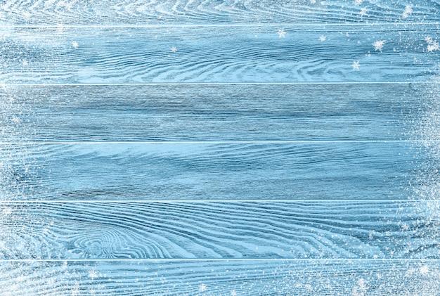 雪とフレークと青い冬ウッドテクスチャ。クリスマスの背景。