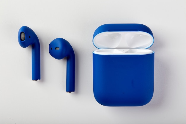 Blue wireless headphones airpods in charging case closeup