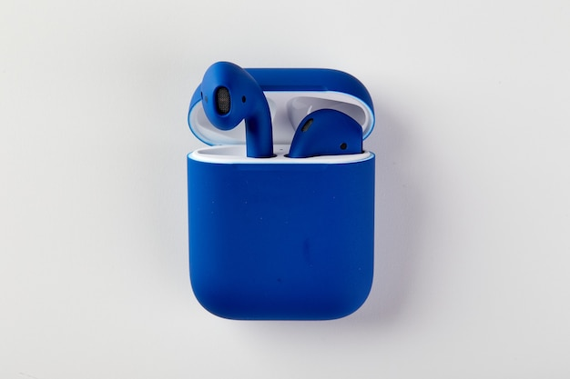 Blue wireless headphones in charging case closeup