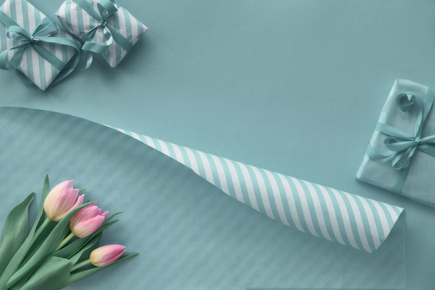 Blue  with pink tulips stripy wrapping paper and gift boxes, copyspace-
