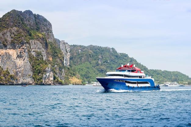 흰색과 빨간색 액센트가 있는 파란색 유람선 열대 섬을 배경으로 바다를 항해하는 유람선