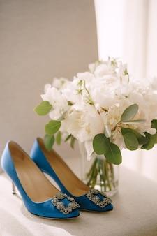 꽃병에 모란 꽃다발 옆에 버클이 달린 파란색 여성용 신발