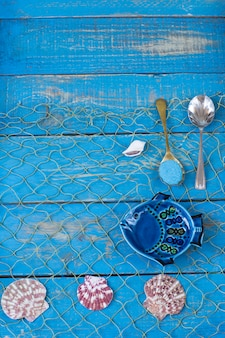 On a blue wooden background fish, shells, spoons with sand.
