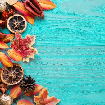 Blue wooden background with autumn leaves and organic products